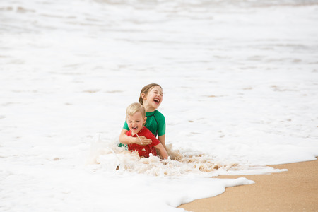 Brother and sister playing in the waves on a tropical beach, dressed in protective wetsuit. Travelling with children, beach hopping, sibling love, beach fun concept. Stock Photo