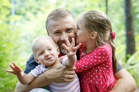 Devoted father hugging his son and daughter, enjoying the outdoor. Family love and bonding, active lifestyle, fathers day concept. Banco de Imagens
