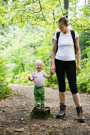 Devoted mother holding hands with her son, walking in the woods. Family, active lifestyle, mother-son relationship concept. Banco de Imagens