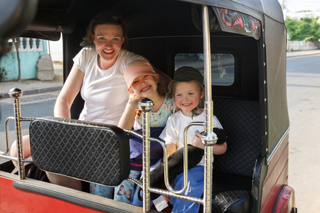 Family on vacation, mother and kids sitting in tuk-tuk, traveling through city, having fun. Travelling with children, backpacking, family time, active lifestyle concept. Banco de Imagens