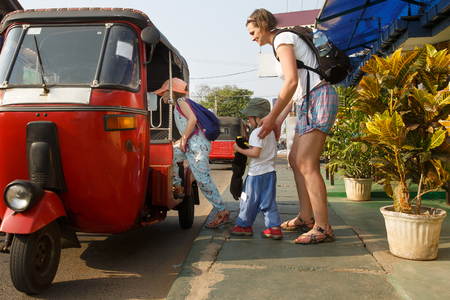 Family on vacation, mother and kids getting in a tuk-tuk, having fun. Travelling with children, backpacking, family time, active lifestyle concept.