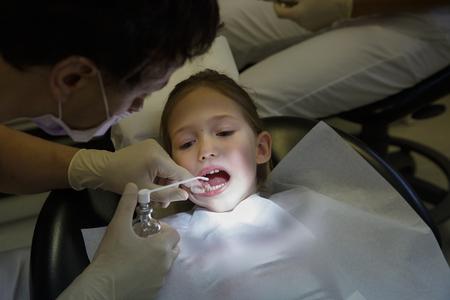 Little girl at dentist office, dentist applying antiseptic for dental treatment. Pediatric dental care concept. Banco de Imagens