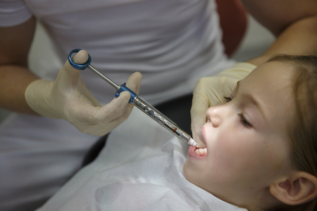 Scared little girl at dentist office, getting local anesthesia injection into gums, dentist numbing gums for dental work. Pediatric dental care concept.