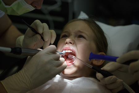 Scared little girl at the dentists office, in pain during a treatment. Pediatric dental care and fear of dentist concept. Banco de Imagens