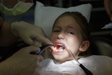 Scared little girl at the dentists office, in pain during a treatment. Pediatric dental care and fear of dentist concept.