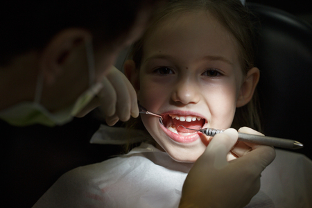 Smiling little girl in the dental office, getting her teeth checked by dentist. Prevention, pediatric dental care concept.