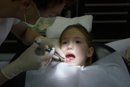 Little girl at dentist office, getting local anesthesia injection into gums, dentist numbing gums for dental work. Pediatric dental care concept.