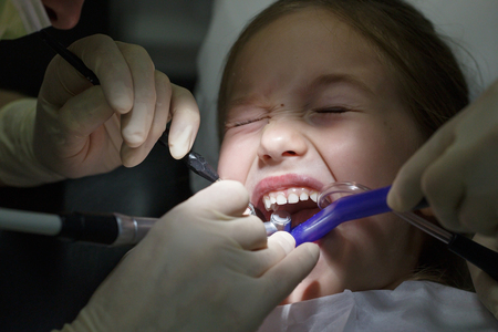 Scared little girl at the dentists office, in pain during a checkup. Pediatric dental care and fear of dentist concept.