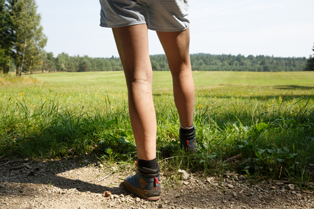 Woman with painful varicose veins on legs resting on a walk through nature. Varices, spider veins problems and active lifestyle prevention concept. Фото со стока - 120145037