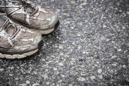 Worn, dirty, smelly and old running shoes on a tarmac road. Road running, endurance, marathon aftermath and active lifestyle concept.