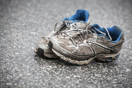 Chaussures de course usées, sales, malodorantes et vieilles sur une route goudronnée. Course sur route, endurance, séquelles de marathon et concept de mode de vie actif.