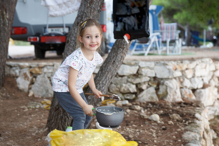 Girl at the campsite, cooking food in outdoor kitchen. Active natural lifestyle, family time, home away from home concept.
