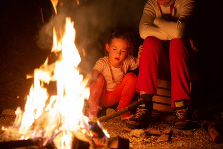 Mother and daughter spending quality time by a self-made campfire during adventurous camping trip, playing with fire. Active natural lifestyle, family time and love concept.