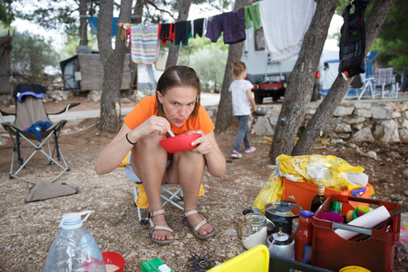 Mother with daughter at the campsite, preparing food in outdoor kitchen, having fun in the outdoors. Active natural lifestyle, family time, home away from home concept. Imagens