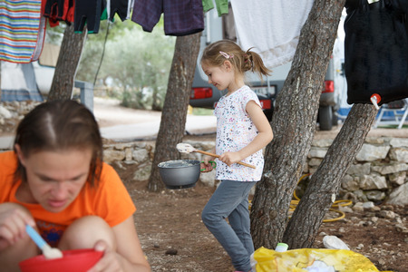 Girl at the campsite, cooking food in outdoor kitchen, having fun in the outdoors, mother eating. Active natural lifestyle, family time, home away from home concept.