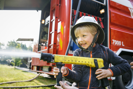 Little boy acting like a fireman holding firehose nozzle and splashing water. Banco de Imagens - 123238134