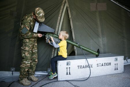 Soldier introducing anti-aircraft air defence simulator to a boy child on army open house day in a military base Imagens