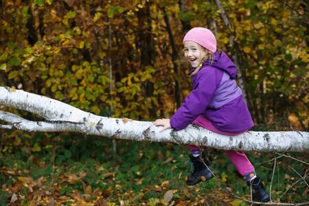 Smiling girl playing in woods, sitting on a birch log