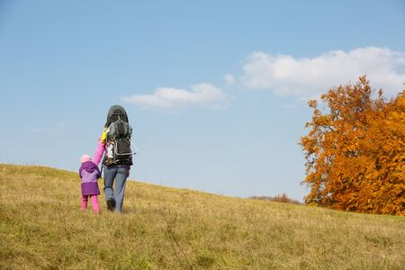 Mother with children in nature on a nice autumn day carrying kid