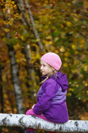 Girl playing in woods, sitting on a birch log Banco de Imagens - 129949812