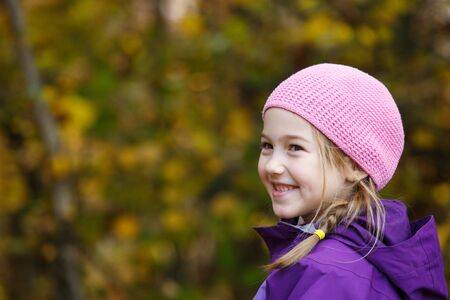 Smiling girl with plait in winter cap enjoying beautiful autumn day Banco de Imagens - 129949813