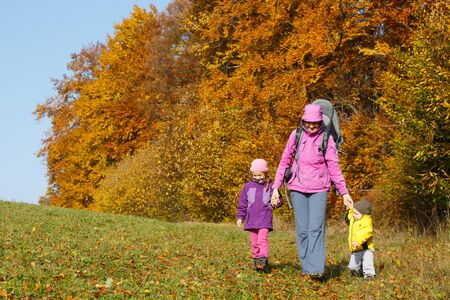 Mother with children in nature on a nice autumn day holding hands