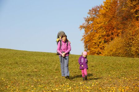 Mother with children in nature on a nice autumn day carrying kid Banco de Imagens - 129949824