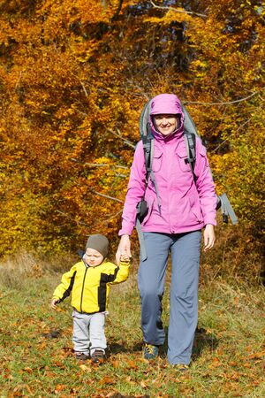 Mother with son in nature on a nice autumn day holding hands