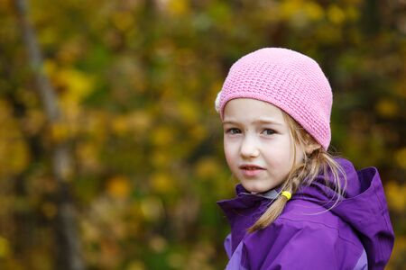 Girl with plait in winter cap enjoying beautiful autumn day