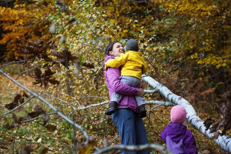 Smiling mother with children in nature on a nice autumn day carrying kid