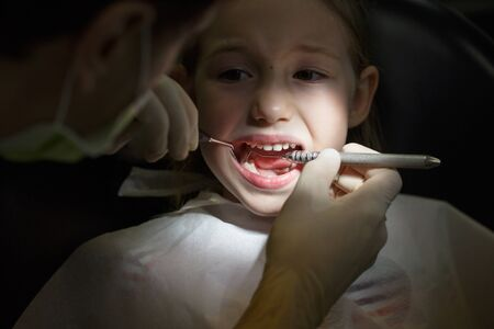 Scared little girl at the dentists office, in pain during a checkup. Pediatric dental care and fear of dentist concept. Banco de Imagens - 137699316