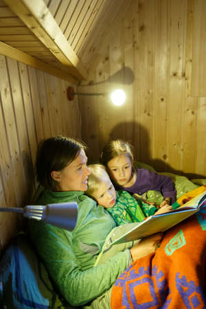 Mother reading bedtime stories to her children before going to sleep. Educational, motherhood, childhood, family concept. 版權商用圖片