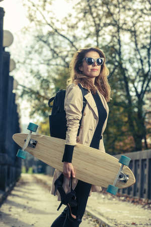 Active woman with longboard. Urban lifestyle concept.