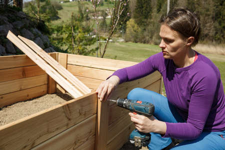 Woman screwing a wooden frame using power drill. DIY concept. Powerful woman.