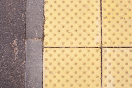Bright yellow tactile paving for the visually impaired on the sidewalk.