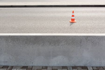 traffic cone on bitumen pavement road for cars with a large concrete fence separating the road and sidewalk 写真素材