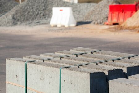 Piled concrete curbstones. Construction material for road construction works. construction background