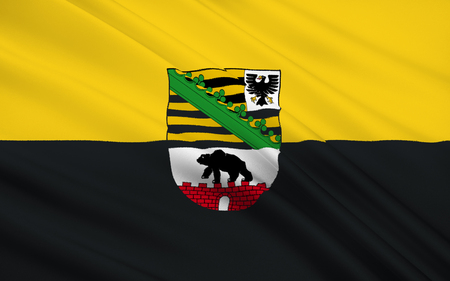 Flag of Saxony-Anhalt is a landlocked federal state of Germany surrounded by the federal states of Lower Saxony, Brandenburg, Saxony and Thuringia. Capital is Magdeburg. Stock Photo