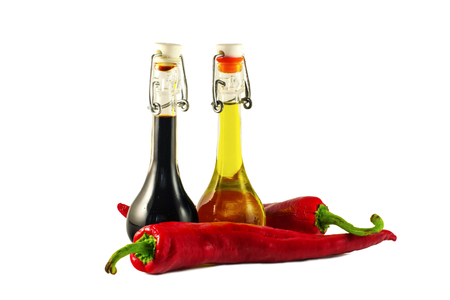 chilly: Two bottles of wine vinegar, olive oiland two red hot chilly peppers  isolated on white background