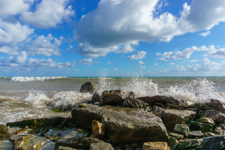Stormy Black Sea, stones and blue sky