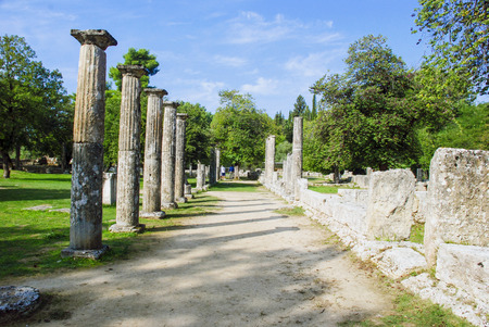 delphi: Tourists on excursion in ancient Olympia in Greece - Palaistra or fighting arena remains near Ruins Filippeyon Stock Photo