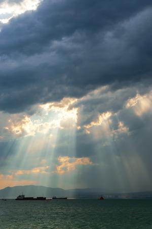 amanecer: Rayos solares rompen a través de las nubes antes de la lluvia