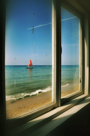 ennui: View from the window of an old thrown house on a boat with red sails, located on the Black Sea coast Stock Photo