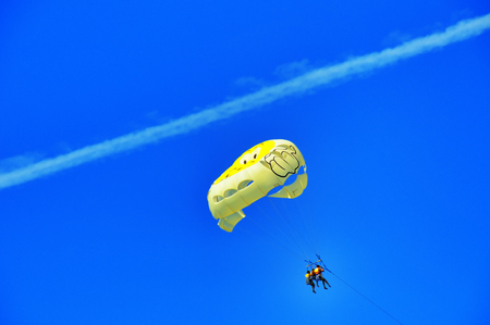 parachutists: Yellow Parachute with three parachutists in the blue sky after passing aircraft