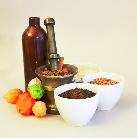 tableware life: Still life of brass and ceramic tableware with spices, cereals and physalis Stock Photo
