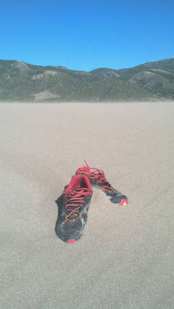 embedding: Shoes embedding in sand dunes Stock Photo