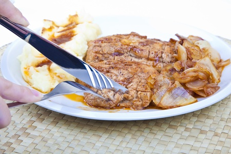 Slicing grilled chicken steak with onions and mashed potatoes