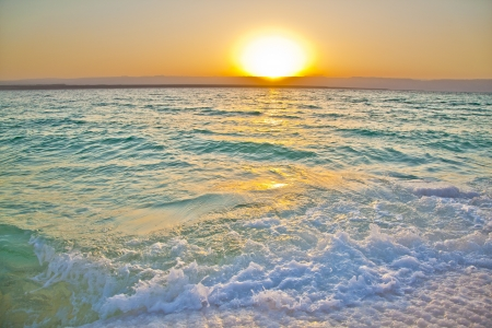 Small waves smashing against salty shores of the dead sea in Jordan Stock Photo