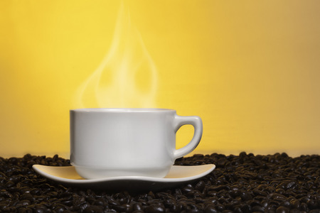 Hot steaming cup of coffee on top of fresh roasted coffee beans.