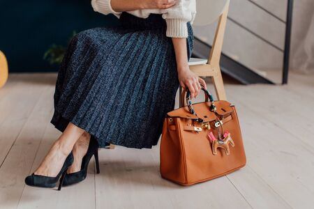 Multi-colored leather bags, in a room with a good interior and beautiful colored furniture, sometimes a girl is in the frame